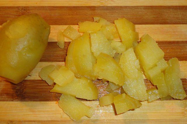 Отварить картофель, очистить и нарезать кубиками.